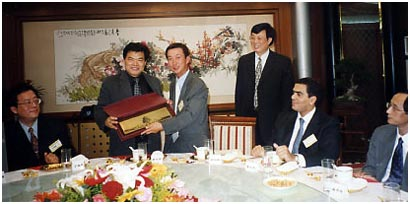 2001年10月, 胡伯橋會長於北京訪問時贈送紀念品給中國保險協會主席唐運祥先生